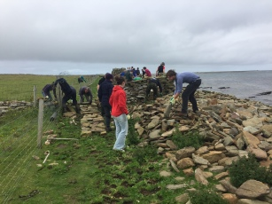 The team start building a new section of dyke wall on firmer ground, a few metres inland from the original wall that was destroyed in winter storms